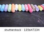 Row of colored chalk on blackboard - stock photo