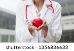 doctor holding a red heart at... | Shutterstock . vector #1356836633