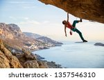Small photo of Caucasian man climbing challenging route going along ceiling in cave at sunset, against beautiful evening view