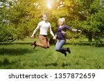 young couple jumping for joy... | Shutterstock . vector #1357872659