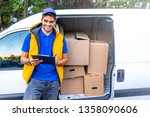 Young male deliverer noting executing of order . Delivery Person. Postman with parcel box. Postal delivery service. Smiling delivery man in red uniform giving a box - courier service concept  - stock photo