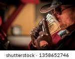 Caucasian Cowboy in Sunglasses and Western Style Hat Sniffing His Money. - stock photo