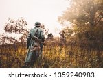 Single Re-enactor Dressed As German Wehrmacht Infantry Soldier In World War II Walking In Patrol Through Autumn Forest. WWII WW2 Times.