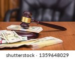 Small photo of Corrupt court. Judge's gavel and bundles of money on the judge's table.Trial of money scammers.