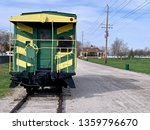 A train caboose sitting by itself on railroad tracks.