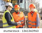 male workers engineers in helmets talking near the bulldozer and excavator - stock photo