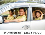cheerful family riding in car | Shutterstock . vector #1361544770