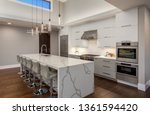 Small photo of Beautiful Modern Kitchen In New Luxury Home. Features Large Waterfall Island with Double Ovens and Hardwood Floors
