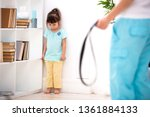 Small photo of Parental punishment. Child abuse. Mom punish a little daughter with a belt and puts her in a corner. Don't hit the kids, help to protect children.