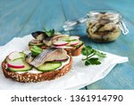 Stock photo smorrebrod sandwich with herring rye bread sliced cucumber radish parsley on paper salted fish in 1361914790
