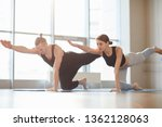 Small photo of Concentrated young couple keeping arm and leg parallel to floor while practicing table pose to lengthen spine