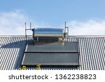 Rooftop solar hot water cylinder or geyser  with photovoltaic cells  on rural house converting the renewable sustainable energy of the sun for electricity and heating