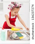 Little girl cleaning the kitchen - wiping the sink area, wearing big hair curls - stock photo