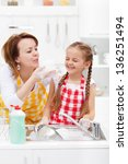 Woman and little girl having fun washing the dishes - playing with the foam - stock photo