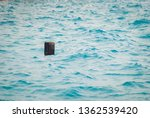 Small photo of Black plastic canister floats in the sea. Household waste, concept of lack of respect for the environment