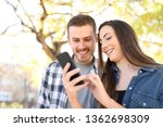 happy couple in a park using a... | Shutterstock . vector #1362698309