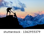 Teamwork couple helping hand, trust in mountains. Team of climbers man and woman hiking, help each other on top of mountain, climbing together, inspiring sunset on Elbrus, Russia.
