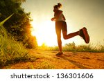 young lady running on a rural... | Shutterstock . vector #136301606