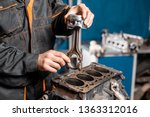 Small photo of Car mechanic holding a new piston for the engine, overhaul.. Engine on a repair stand with piston and connecting rod of automotive technology. Interior of a car repair shop.