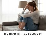 Small photo of Upset woman frustrated by problem with work or relationships, sitting on couch, embracing knees, covered face in hand, feeling despair and anxiety, loneliness, having psychological trouble