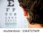 Small photo of Concept photo of myopia or nearsightedness as diseases of eye and the optical system. In the background blurry fuzzy table for testing visual acuity, in the front - head of the person in focus closeup