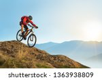 Cyclist in Red Jacket Riding the Bike in the Beautiful Mountains Down the Rock on the Sunrise Sky Background. Extreme Sport and Enduro Biking Concept. - stock photo