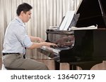 a young man playing piano on...   Shutterstock . vector #136407719