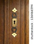 Small photo of brass key doorplate on fragment of wooden door