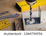 Carpenter drills a hole with an electrical drill on a wooden plank, close up. Battery screwdriver or drill - stock photo