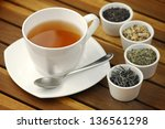 Stock photo cup of tea with different sorts of tea leaves in bowls 136561298