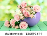 Stock photo pot with flowers on a wooden table on the nature background 136593644
