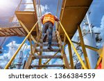 Small photo of worker, engineering wearing safety shoe with set of safety and security regulation, walking in mind step on the steel gangway bridge at workplace, working in high stage & level of insurance