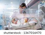 Small photo of Female doctor examining newborn baby in incubator. Night shift