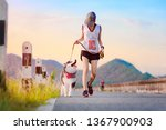 Stock photo woman doing daily exercise jogging on the public park road with puppy breed dog dog asking for 1367900903