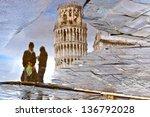 PISA, ITALY - MARCH 18: reflection of the leaning tower and couple of unidentified tourists in a puddle on March 18, 2013 in Pisa.Place of Miracles is a UNESCO World Heritage Site since 1987 - stock photo
