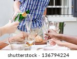 Man pours champagne into glass flutes held by hands of multi racial origins, no faces - stock photo