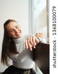 smiling young woman sitting at...   Shutterstock . vector #1368100079