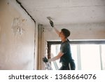a man removes old paint from... | Shutterstock . vector #1368664076