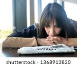 Small photo of Beautiful brunette woman struggles to find the answer while doing a crossword in a newspaper