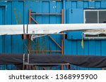 Small photo of Cambridge, Cambridgeshire, UK - Circa April 2019: Pair of 2-man scull boats seen hung up on a metal frame next to a blue painted metal office. Located at a boatyard, one can be seen covered.