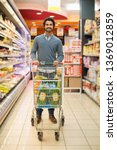 handsome man shopping in a... | Shutterstock . vector #1369012859