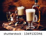 Coffee with Irish whiskey and whipped cream in glass on rustic wooden surface - stock photo