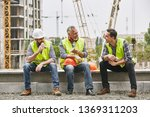 Time for a break. Group of builders in working uniform are eating sandwiches and talking while sitting on stone surface against construction site. Building concept. Lunch concept - stock photo