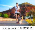 Stock photo woman doing daily exercise jogging on the public park road with puppy breed dog 1369774193