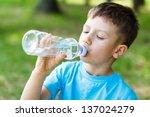 little boy drink water  outdoor | Shutterstock . vector #137024279