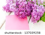Lilac branch with card  on wooden table - stock photo
