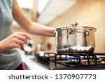 Beautiful young woman housewife prepairing dinner, hold in hands big steel saucepan, standing it on gas-stove.