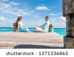 Couple sitting far away at the wooden pier in front of each other, and looking each other. Turquoise water behind them. Romantic concept.