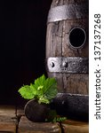 Small photo of Old oak wine barrel with fresh young vine leaves balanced on the bung off a grapevine standing on old bricks against a dark background with copyspace
