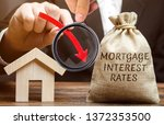 Small photo of Bag with the money and the word Mortgage interest rates and arrow down and house. Low interest in mortgages. Reducing interest payments for mortgages. The fall in housing rates on credit. Analysis
